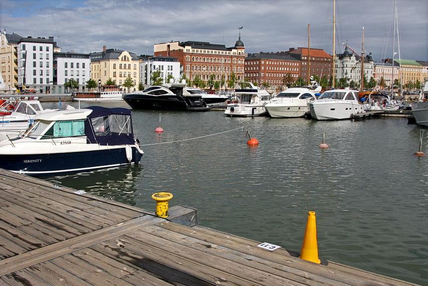 Foto da marina com vários barcos ancorados e prédios ao fundo