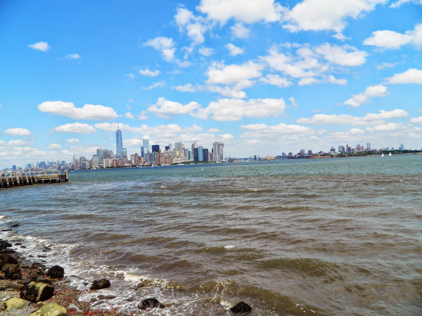 new york city skyline from statue of liberty clear day beautiful sun finance district beach shore