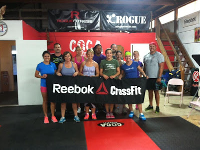 A crowd of athletes at Coca CrossFit hold up a Reebok CrossFit sign