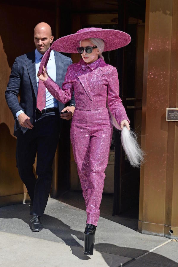 Glittered in a pink suit, big hat with a pair of her signature platform black shoes.