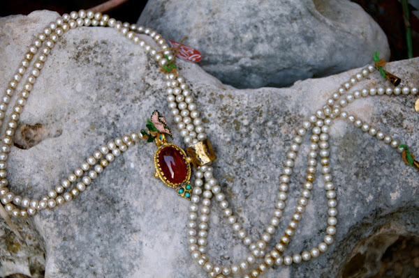 Strands of fresh water pearls lariat around a beautiful stone and crochet and brass accents...