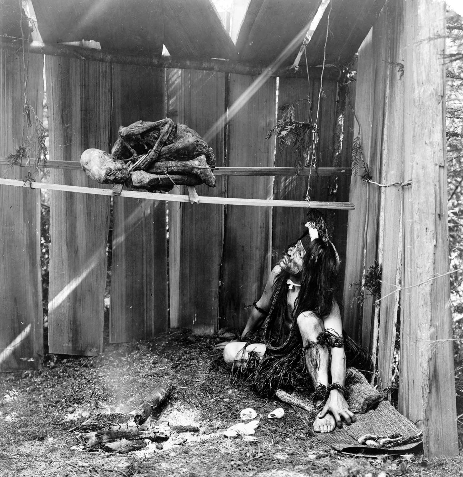 Kwakwaka'wakw man inside board structure, curing mummy over smoke and coals of fire, 1910.