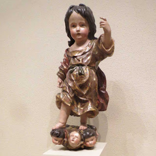 Wooden painted sculpture of a young child standing on disembodied heads of smaller children