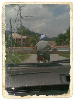 Pak aji menunggang motor membawa kayu panjang