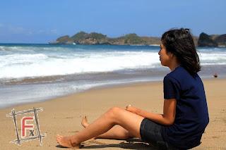 wanita di pinggir pantai bajul mati