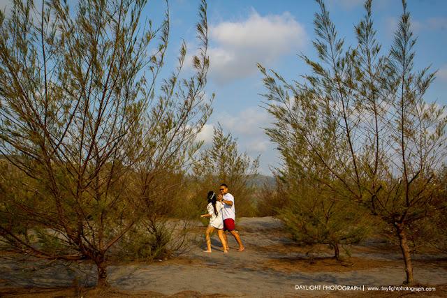 foto prewedding, pasangan sedang berjalan sambil bergurau diantara pohon-pohon cemara di gumuk pasir jogja