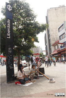 músicos callejeros tocando cordófono tambor y shenai en liberdade sao paulo brasil
