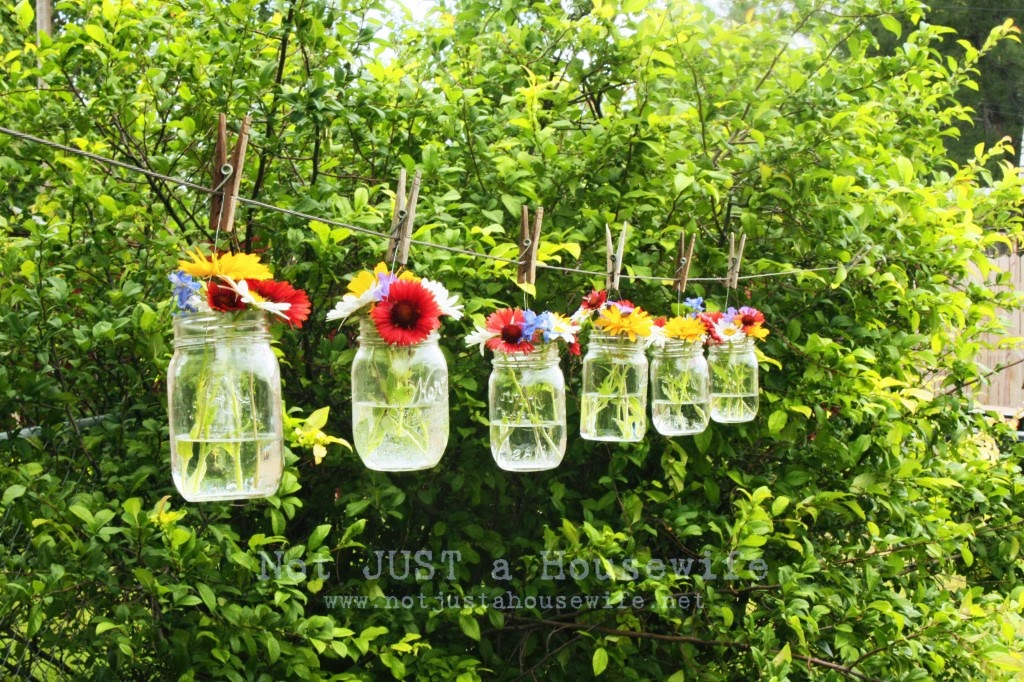 Hanging mason jars with flowers in them