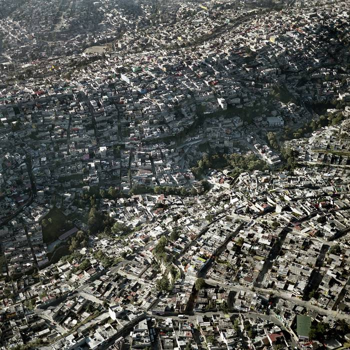 Unbelievable aerial photographs of Mexico City show how the urban landscape spreads over mountains while maintaining a remarkable 25,400 people per square mile.