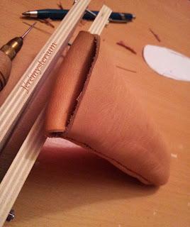 Détails sur le fermoir, simple languette de cuir rabattue, du porte couteau.
