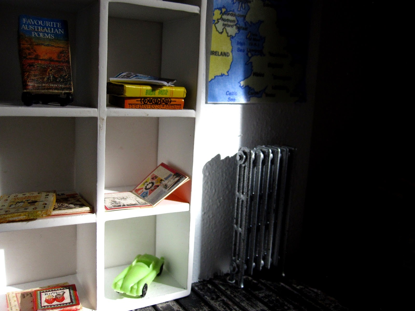 Sun shining on a bookcase in a modern dolls' house miniature pop-up Little Library,