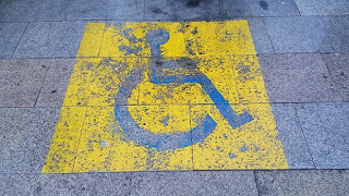 Señal de Discapacidad pintada en el suelo. El fondo del icono es amaillo y el símbolo de la persona en silla d ruedas en azul.