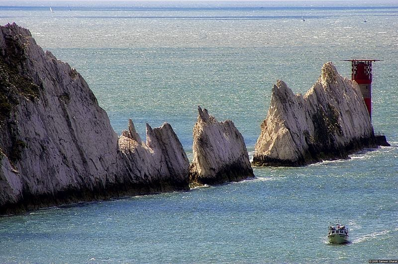 """The Needles"" are chalk stacks jutting out of the sea at Alum Bay on the western end of Isle of Wight, England. There's a gap between these chalk stacks where a narrow pillar or chalk used to stand until it was destroyed in a storm in 1764. This narrow pillar gave this site its name, ""The Needles""."