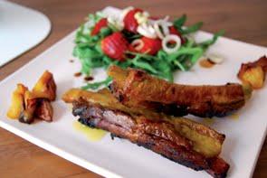 Costine di maiale con mele e zafferano su insalata di rucola, fragole e porri