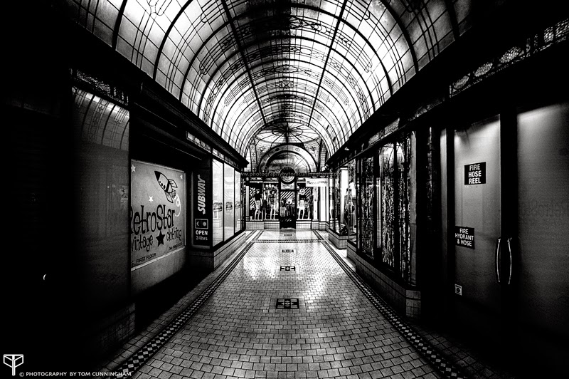 A wide angle photograph in black and white by Tom Cunningham of a grungy shopping arcade off Flinders Lane in Melbourne