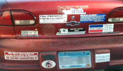 Back of a red Chevy Cavalier, Minnesota plate, covered in bumper stickers