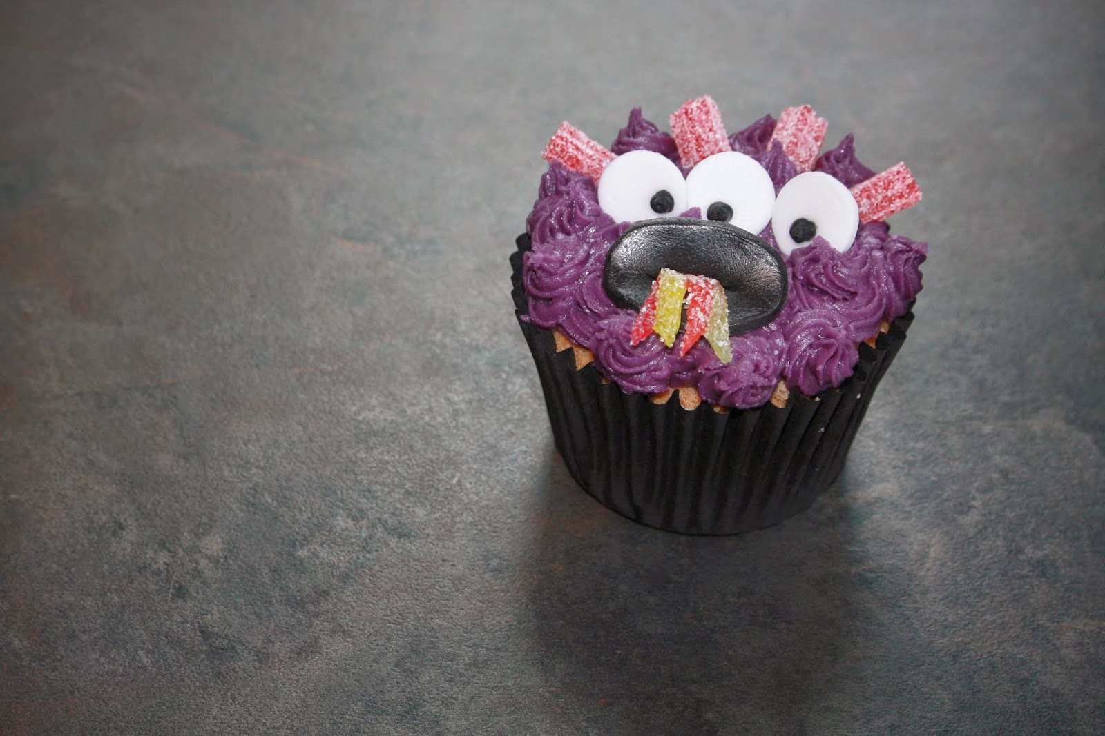 Purple monster cupcake sticking out his multi-coloured tongue!