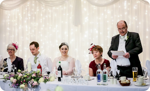 Top table at wedding with white light curtain behind it