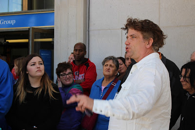 Guide David Loftson speaks to visitors outside the Bank of Montreal.