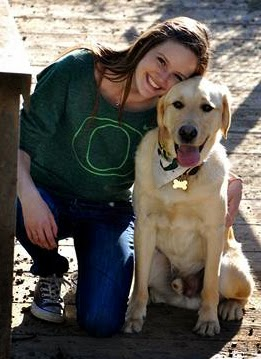 Maddie wears a University of Oregon green sweatshirt and puts her arm around a yellow Lab smiling.