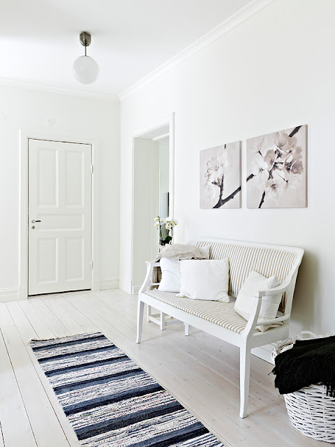 White Gustav style bench in a white foyer with a blue, white and black striped rug