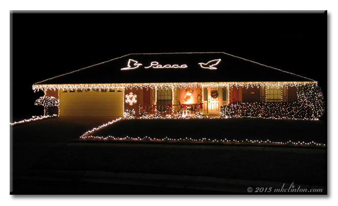 House decorated in Christmas lights with PEACE on the rooftop.