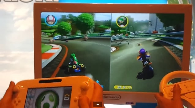 Two-player split-screen mode in Mario Kart 8. The gamer on the left is using the Wii U GamePad to play, while the person on the right is using the Wii Wheel.