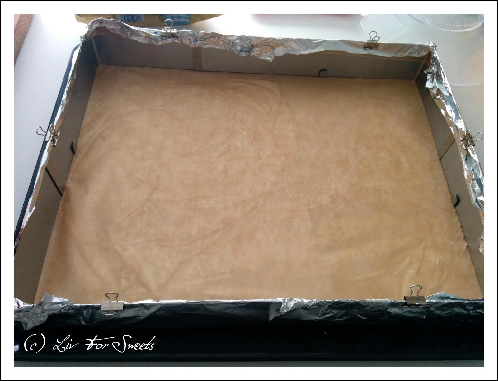 Backrahmen ausgelegt mit Backpapier und umspannt mit Alufolie, die mit Maulklemmen befestigt ist