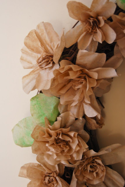 "Paper flowers on one side of a large wreath. I like to think of these flowers as representing the differing flower forms in the Peony family... single, semi-double, fully double, Japanese, Anemone and ""bomb"" shaped."
