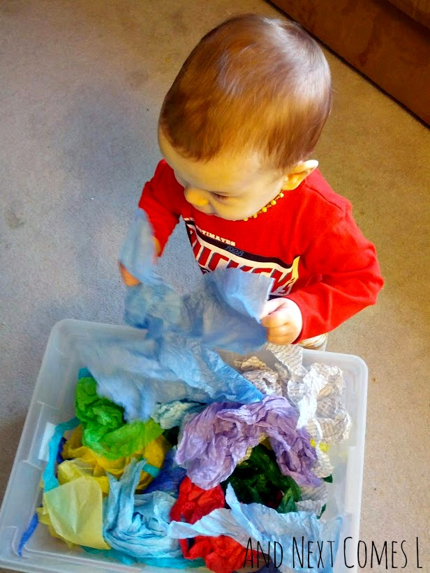 Simple toddler sensory bin using tissue paper from And Next Comes L