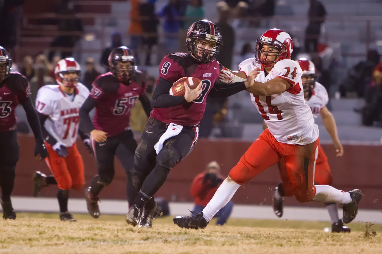 Ballard Quarterback, Rex Wallace, evades a tack from Damien Sm ith, 14, of  the Dupont Manual Crimsons. November 8, 2013.(Matt Herp/Special to the ...