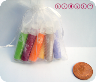 Image of seven mini Balm Balm single note perfumes in white organza bag with two pence piece in the foreground