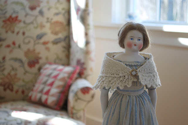 antique china doll with knitted shawl
