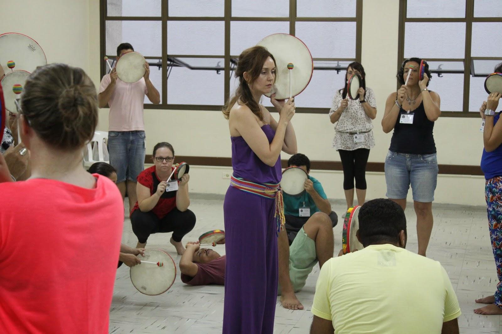 Descrição da Foto: Participantes estão tocando o tambor. Eles estão posicionados em três posições: baixo, médio, alto.