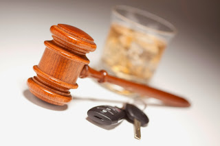 A gavel, an alcoholic drink and car keys.