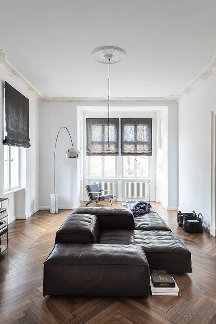 Salón con sofá en el medio y lámpara Arco
