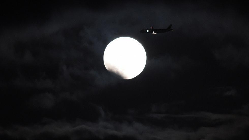 Самолет летит на фоне Луны в начале полного лунного затмения