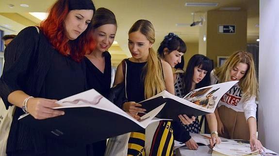 Alumnas de Art&Fashion revisan sus bocetos.