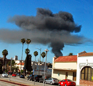 Smoke rises in sky from burning building