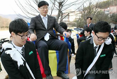 Estudiantes surcoreanos llevando a sus profesores en palanquín