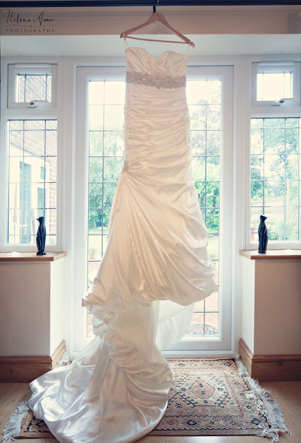 bride dress hung up in window before the ceremony