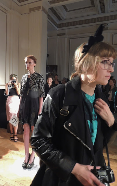 Blogger walks past model during Hellen Van Rees' S/S14 presentation