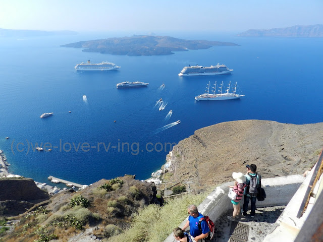All sizes of ship sit in the harbour below Fira in Santorini