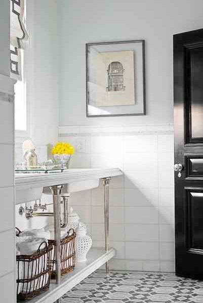 Bathroom with a black lacquer door, mosaic tile floor, and chrome sink