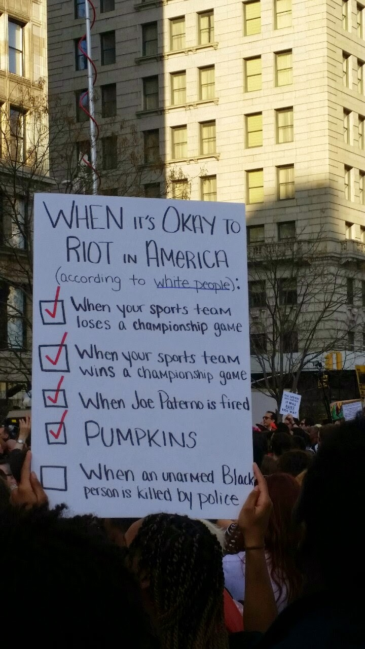 "Picture of a protester holding a sign that reads ""When It's Okay to Riot in America"" with checked boxes for sports and other events but an unchecked box by ""When an unarmed Black man is killed by police"""
