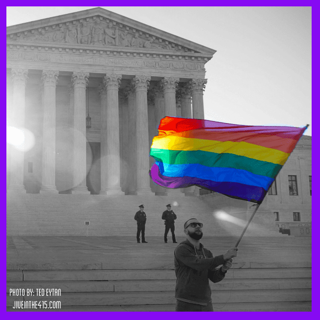 An anonymous man waves the rainbow flag in front of the US Supreme Court Building in Washington, DC on April 28, 2015.