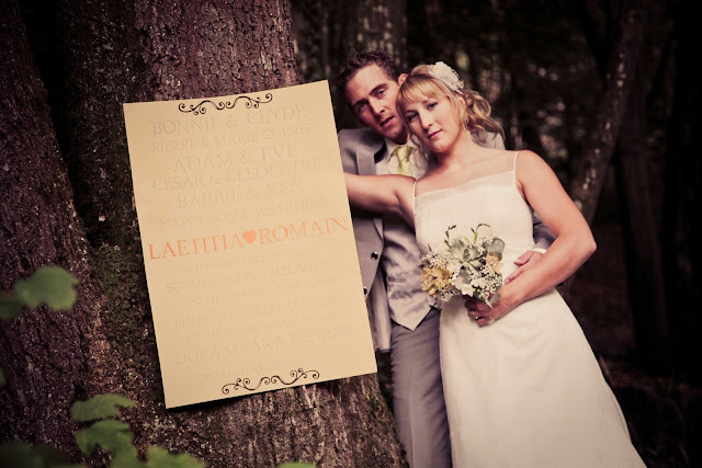 A bride and a groom next to a tree in a forest
