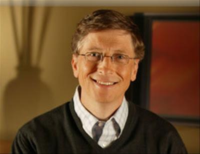 Descrição da foto: Bill Gates, homem de meia-idade, cabelos loiros escuros, curtos, pele e olhos claros. Na foro usa óculos de grau e está sorrindo tranquilamente olhando fixo para câmera. Veste uma camisa xadres e sobre ela um suéter escuro de lã; O fundo é em tons marrons com a sombra na parede de um vaso de flores do lado esquerdo.