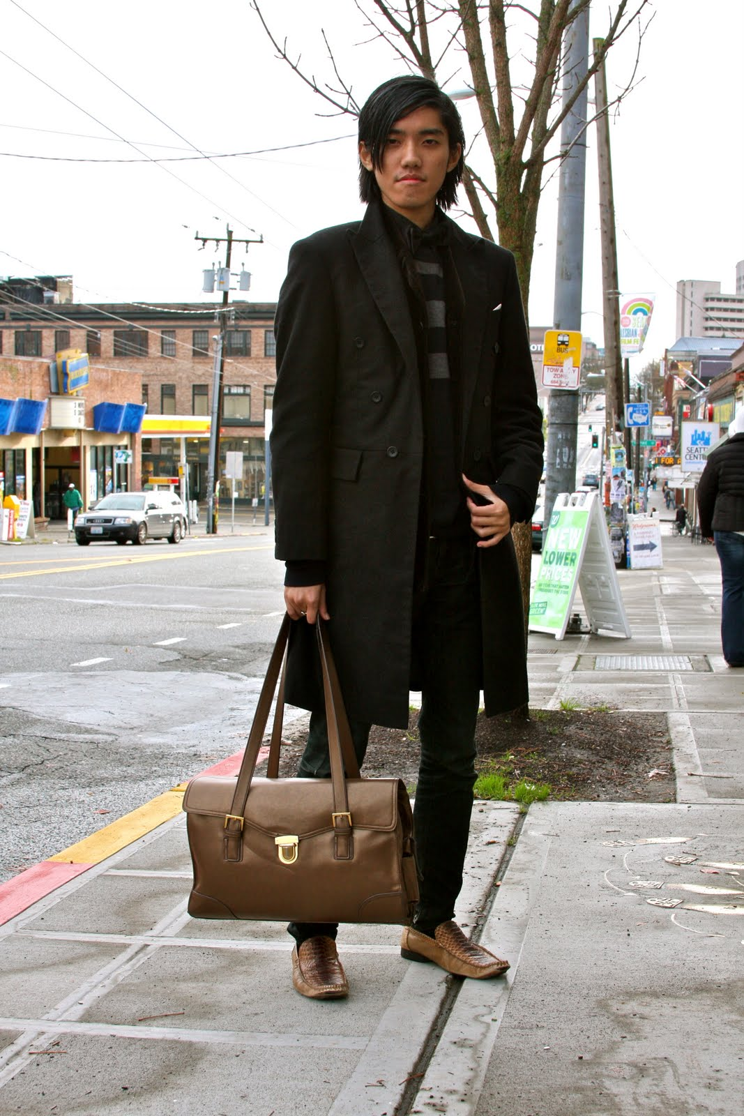 Dio, University of Washington Student wears an all black and brown ensemble featuring a black tailored peacoat over a black shirt with a black bowtie and a grey and black striped sweater; black jeans and a pocket knife; brown bag and brown reptile leather loafers.
