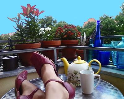 Blauer Himmel, blaue Vasen, rote Lilien und Gerbera (?) ... dazu Füße auf dem Tisch, daneben Teekanne und -tasse
